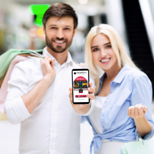 Shopping App. Smiling Couple Showing Blank Cellphone Screen Standing In Mall Center. Mockup, Shallow Depth